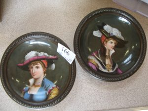 Lot 166 - Two painted Berlin plaques of ladies wearing hats - Sold for £80