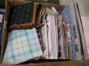 Lot 215 - Box of cross stitch charts and fabric squares - Sold for £25